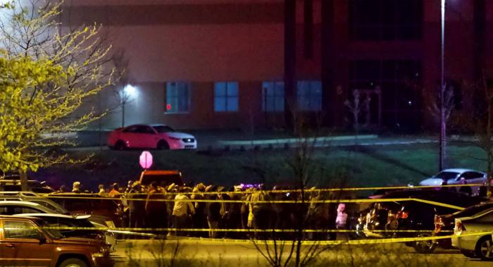 People stood outside a FedEx facility near Indianapolis International Airport after a shooting with multiple victims