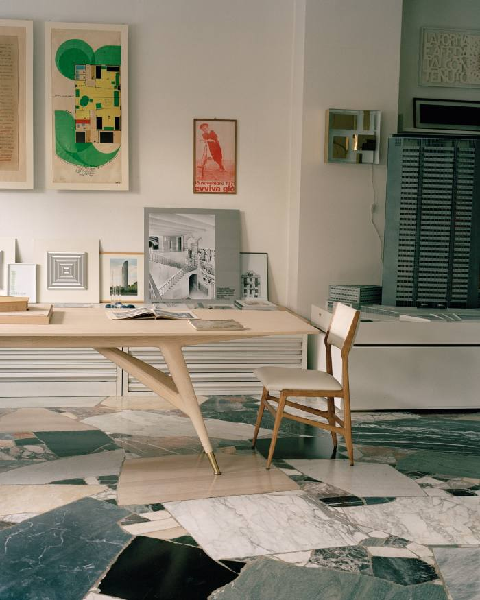 The main space in the Gio Ponti Archives, housed in Ponti's Via Dezza studio, with a D.859.1 table, reproduced by Molteni&C, and a 687 chair, designed for Cassina. On wall (from left), a 1970 study for tall buildings, a poster printed for his 80th birthday party, the Quadro Luminoso lamp he designed for Arredoluce in 1957, and a model of the Pirelli Tower