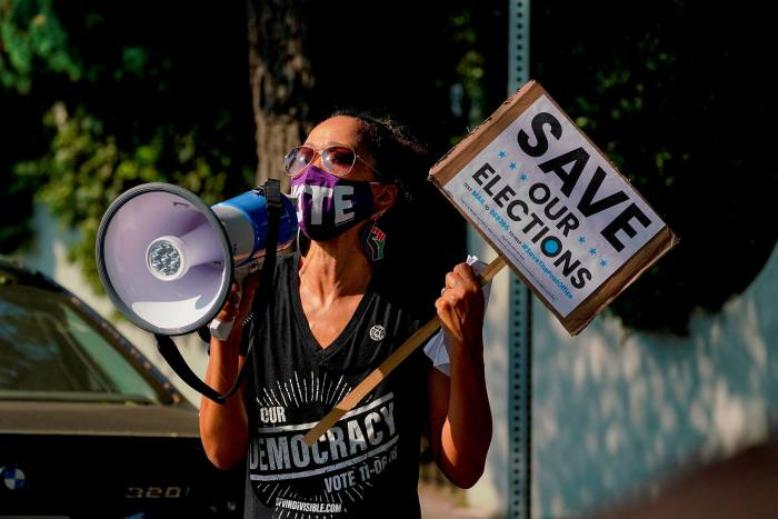 A protester at a 'save the Post Office' demonstration in Los Angeles. Many investors are concerned by the risk that Donald Trump could refuse to accept a defeat in the presidential election