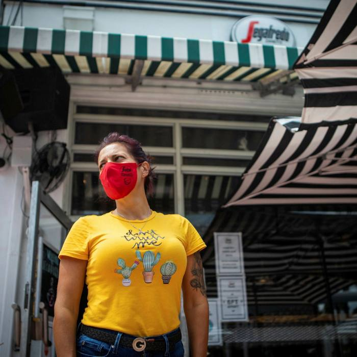 An employee wears a protective mask while waiting to seat customers outside a restaurant in Miami Beach, Florida