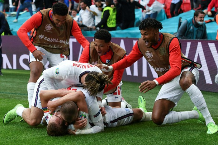 England captain Harry Kane, bottom, disappears under his  team mates after heading in his side's second goal