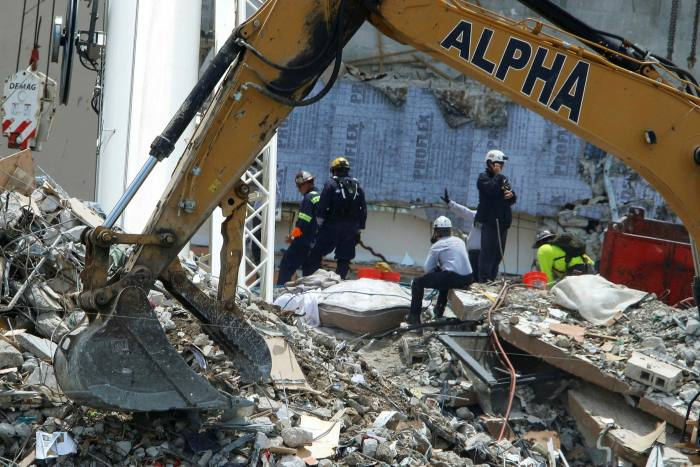 Emergency rescuers conduct search and rescue work at the scene of a partially collapsed residential building in Surfside