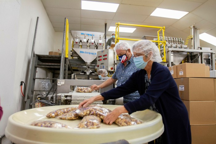 Don and Kim Peacock pack nuts at GNS Foods in Arlington, Texas. Their wholesale business, supplying airlines, evaporated almost overnight when the Covid-19 pandemic started