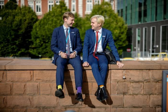 Two young men in blue suits chat while attending the recent Tory conference in Manchester