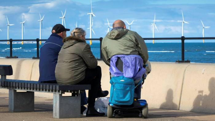 People sit on a bench on the Redcar Promenade