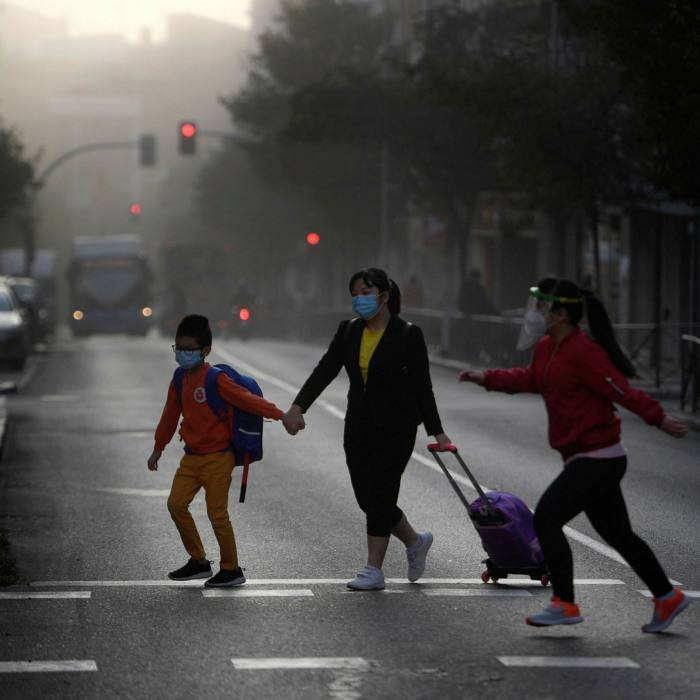 A woman takes children to school in a neighbourhood under partial lockdown in Madrid