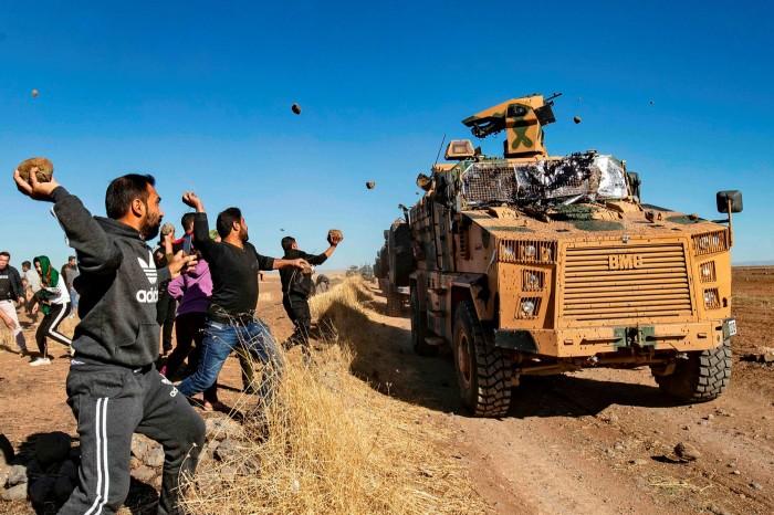 Курдские демонстранты забрасывают камнями турецкую военную машину в ноябре 2019 года во время совместного турецко-российского патрулирования на границе Сирии с Турцией © Souleiman / AFP via Getty
