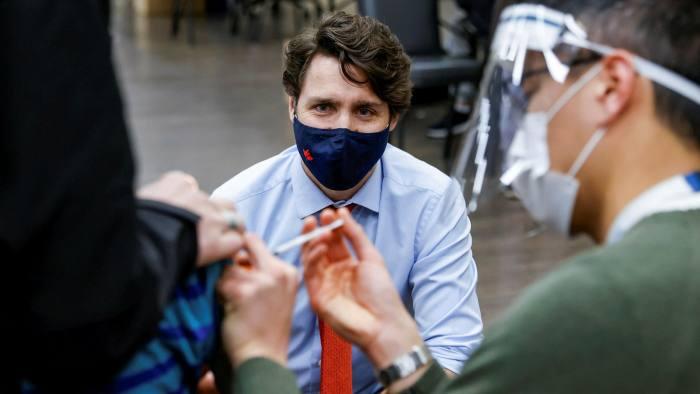 Vaccinated: Justin Trudeau observes a patient receiving a Covid jab — Blair Gable/Reuters