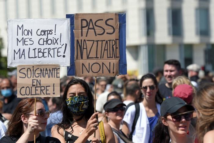 Les gens tiennent des pancartes pour protester contre les nouvelles mesures de sécurité contre les coronavirus, y compris un laissez-passer sanitaire obligatoire