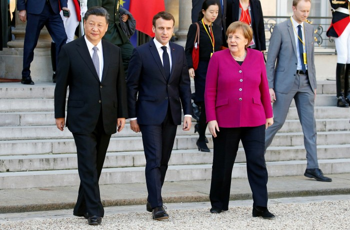 French President Emmanuel Macron (C) with Chinese counterpart Xi Jinping and Germany's Angela Merkel after their meeting at the Elysee Presidential Palace in 2019