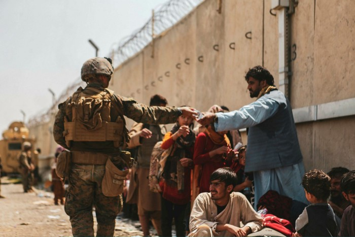 A US Marine hands a bottle of water to an Afghan evacuee.  UK defence secretary Ben Wallace has suggested that those trying to flee should now approach land borders rather than attempting to reach the airport