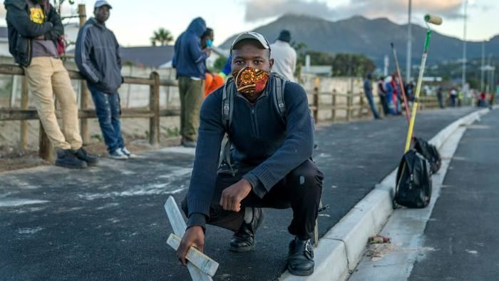 Construction workers wait for work at a road junction in Cape Town in June