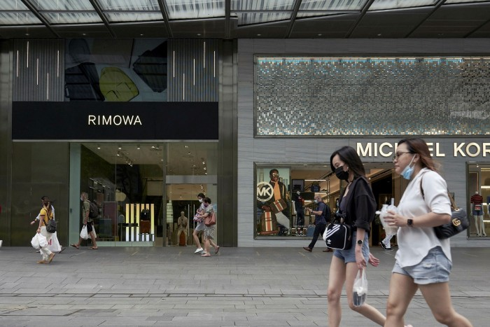 Pedestrians pass a shopping mall in Singapore's Orchard Road