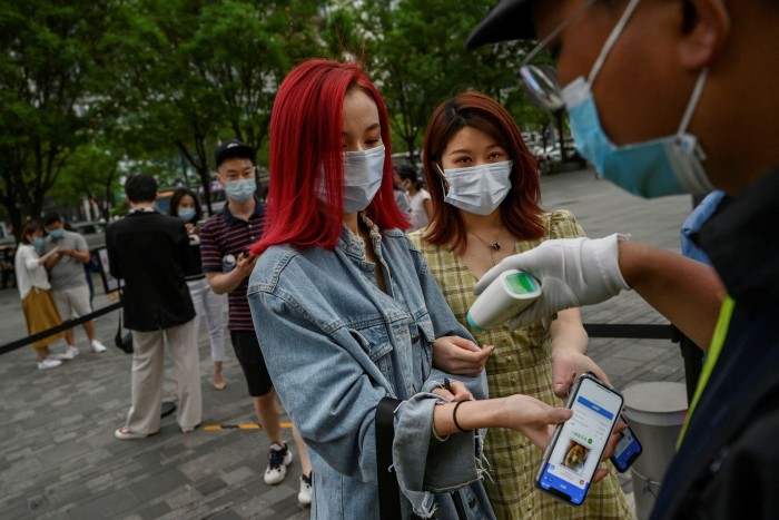 A Chinese woman shows her local health QR code to a security guard as he checks her temperature before entering a shopping area.