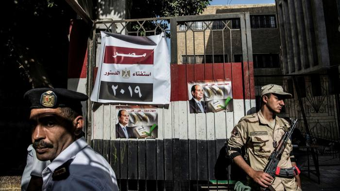 An Egyptian soldier and policeman stand guard at a polling station