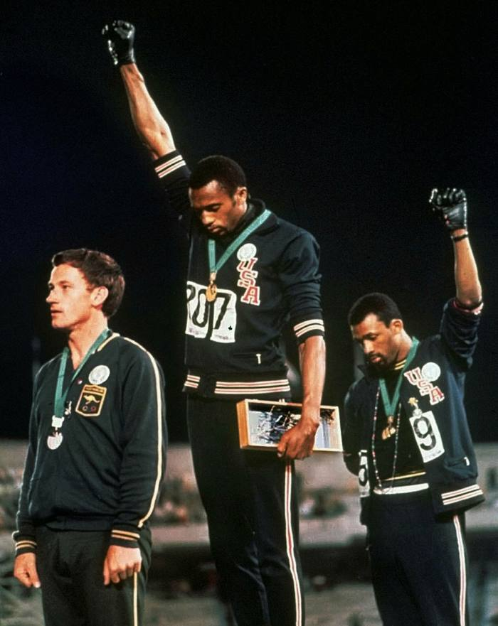 Medallists Tommie Smith, centre, and John Carlos extend gloved hands skyward during the US anthem at the 1968 Olympics in Mexico City