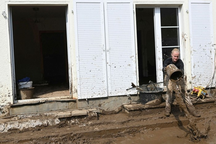 A resident clears mud from a building in Insul, near Bad Neuenahr-Ahrweiler in Germany's Rhineland-Palatinate state