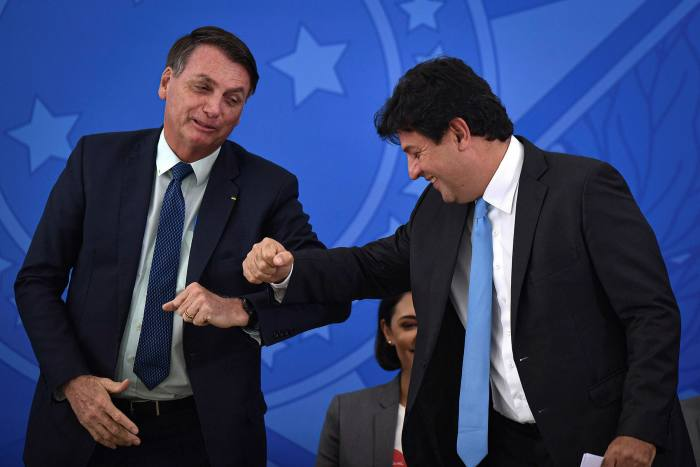 President Jair Bolsonaro, left, with outgoing health minister Luiz Henrique Mandetta. The Brazilian leader has played down the risks of the virus