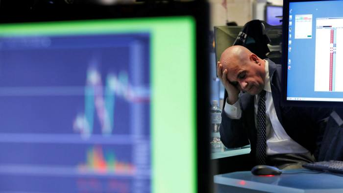 A specialist rests his head in his hand as he works on the floor of the New York Stock Exchange