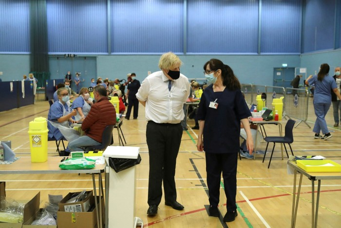 Boris Johnson speaks with a health worker during a visit to the vaccination centre at Cwmbran Stadium in Wales. The prime minister is set to announce a 'road map' for lifting restrictions on Monday