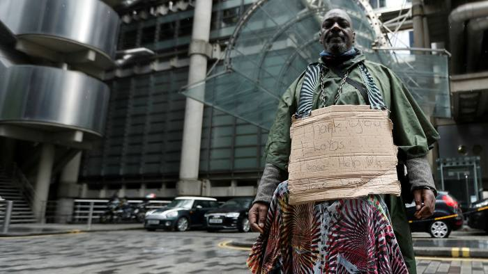 Demonstrator Clapper Priest protests in front of the Lloyd's Building in the City of London on Thursday. In a statement, Lloyd's said: 'We are sorry for the role played by the Lloyd's market in the 18th and 19th century slave trade'