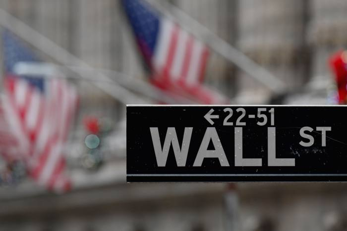 A Wall Street sign outside the New York Stock exchange (NYSE) at Wall Street after heavy rainfall on November 30, 2020 in New York City.