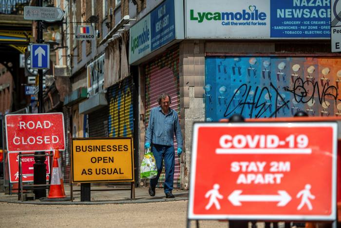 A pedestrian walks past shut shops in Stockport last month