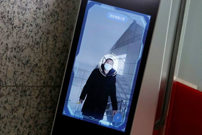 A man has his face scanned by a facial recognition device that identifies people when they wear masks to gain access to the office of the Chinese electronics manufacturer Hanwang (Hanvon) Technology in Beijing