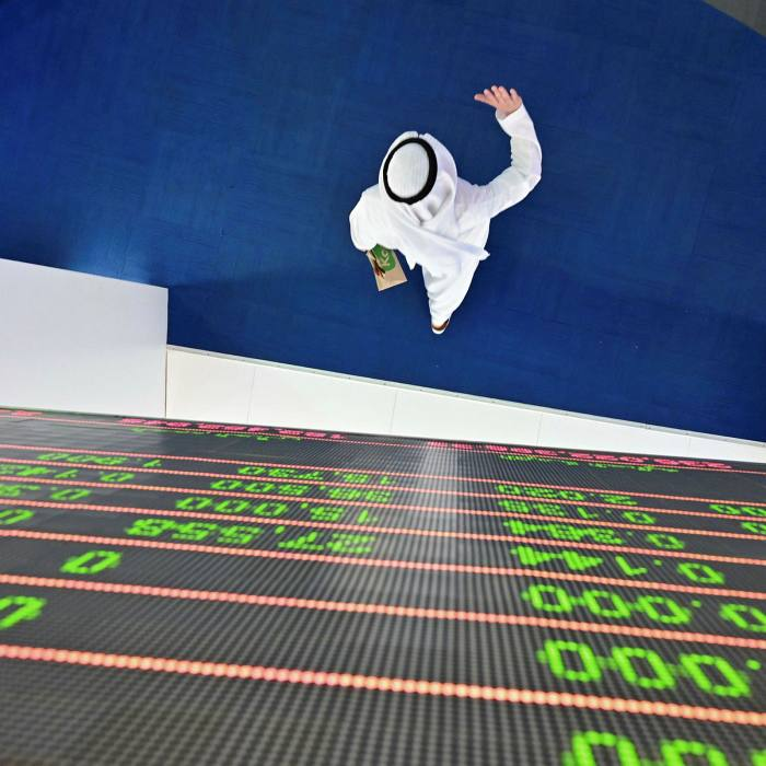 A trader walks beneath a stock display board at the Dubai Stock Exchange