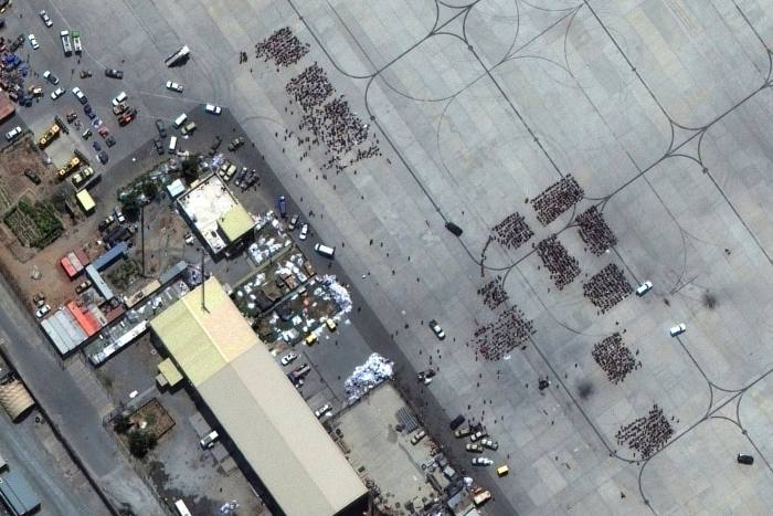 Groups of people wait on the tarmac at Kabul's airport on Monday