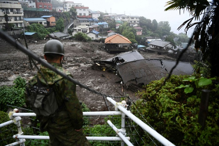 Aftermath: a soldier looks at the wreckage left by a landslide in Atami earlier this month