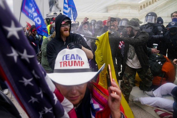 A woman wears a hat with the words Team Trump, as rioters try to break through a police barrier