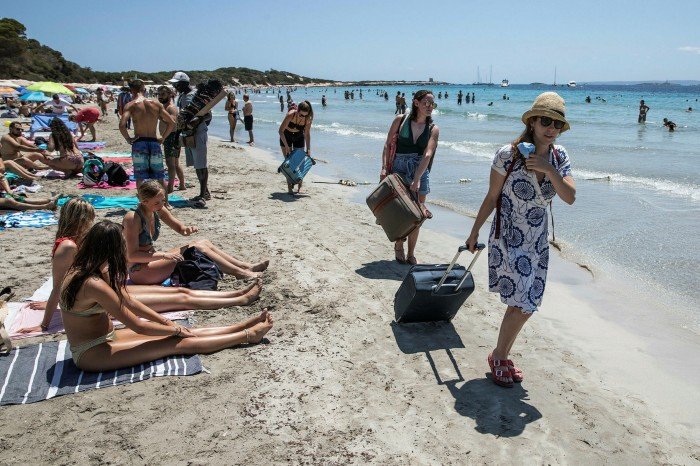 Tourists leave a beach in Ibiza. Spain only expects foreign tourist revenues to reach half their pre-pandemic levels this summer, up from a fifth last year