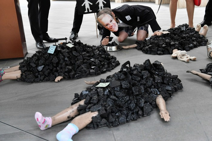 A protester wearing a face mask depicting Prime Minister Scott Morrison eats fake coal out of a dog bowl during an Extinction Rebellion protest in Brisbane last month