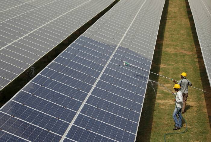 Workers clean photovoltaic panels inside a solar power plant in Gujarat, India