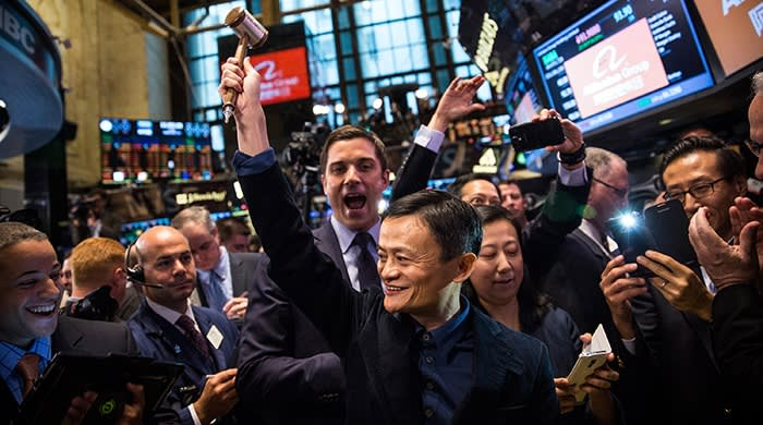 Jack Ma, his arm raised, is surrounded by a crowd at the New York stock exchange at Alibaba's initial public offering in 2014