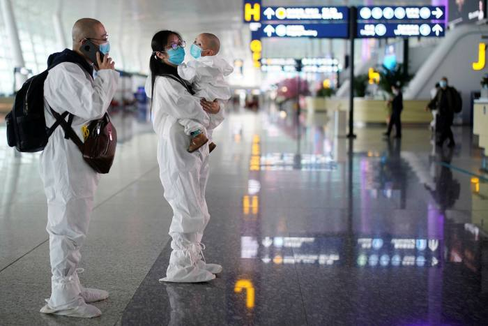 Travellers in protective suits at Wuhan Tianhe International Airport after the lockdown was lifted