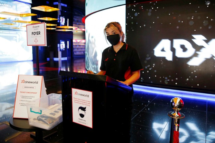 A Cineworld employee wears a mask at the chain's Leicester Square cinema in London