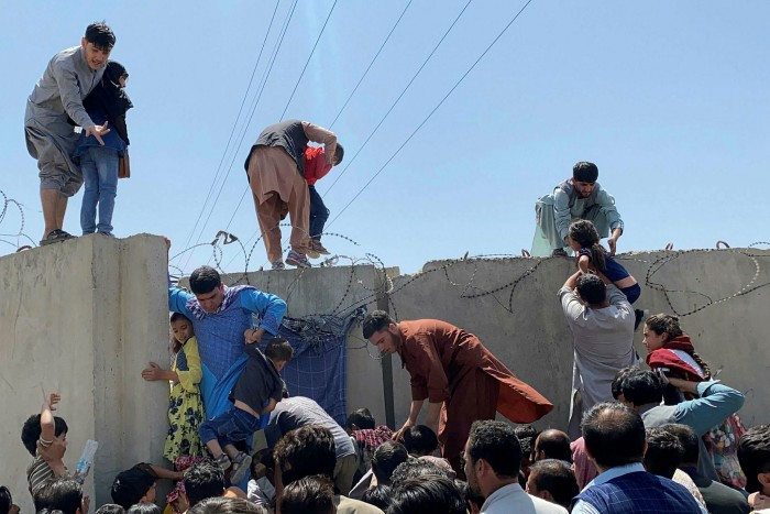 People try to scale the boundary wall of the airport on Monday