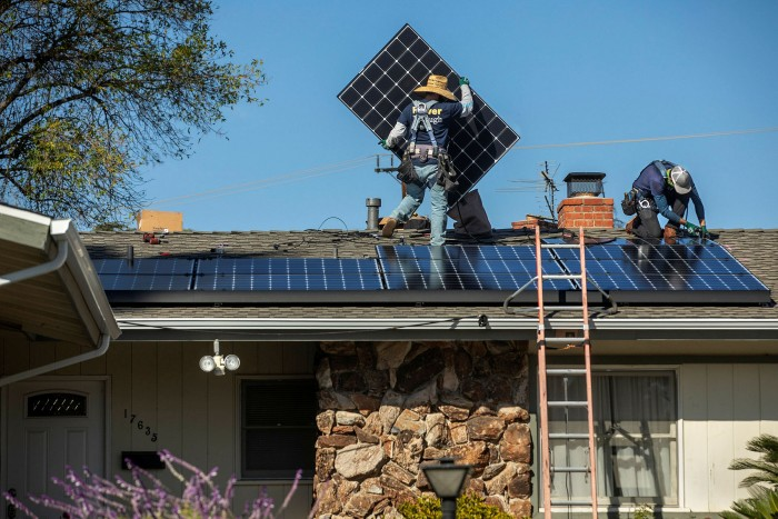 Workers install solar panels on a residential rooftop. Rebates and incentives have encouraged their installation