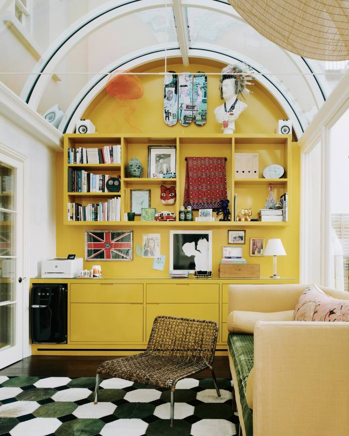 Dawn's office in the conservatory features three Basquiat skateboards at the top ofthe yolk-yellow wall