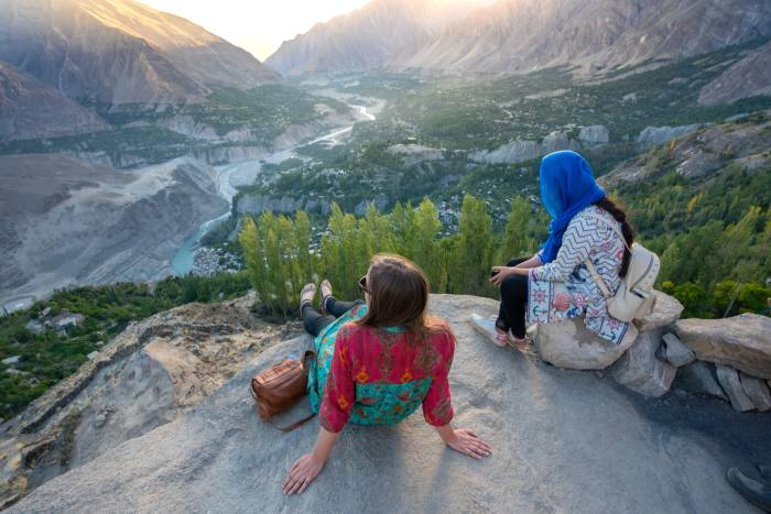 A female traveller and local guide take in the beauty of the Hunza Valley