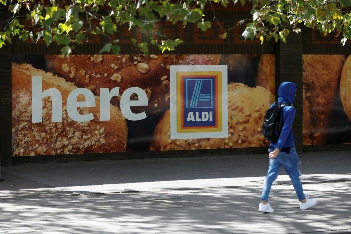 A pedestrian walks past a sign advertising an Aldi superstore in London