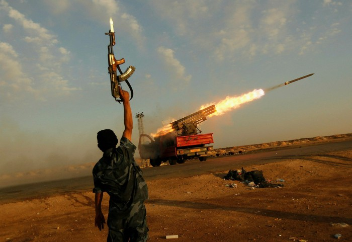 A Libyan rebel celebrates as his comrades fire a rocket at Gaddafi's troops in 2011. Stories of brutality and abuse are common among the thousands of people who have passed through the country since the dictator was overthrown