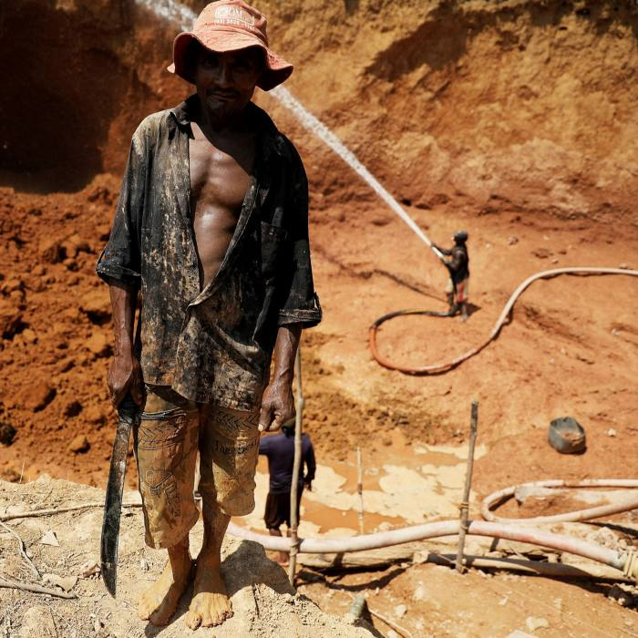 A 'garimpeiro' holds a machete at a wildcat gold mine at a deforested area...