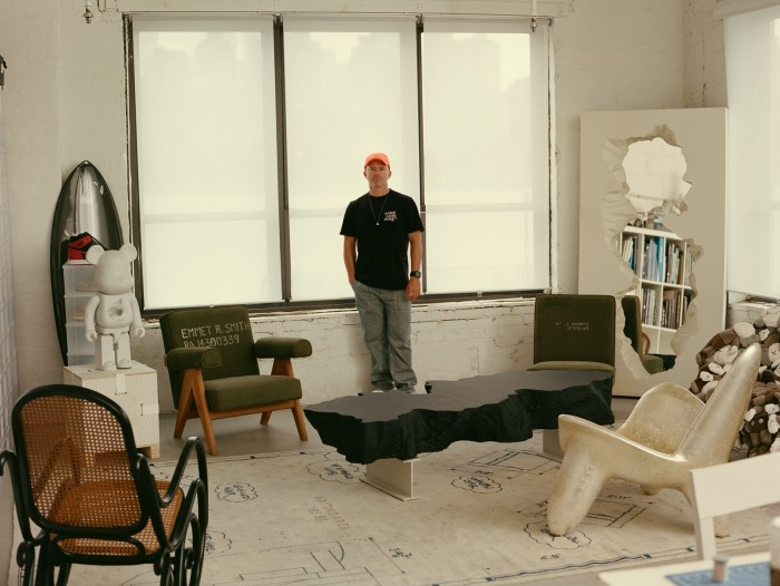 Arsham in his studio.  To the left is the Snarkitecture x Bearbrick with the Haydenshapes x Arsham collaboration surfboard behind it.  The Wendell Castle Triad chair is on the right