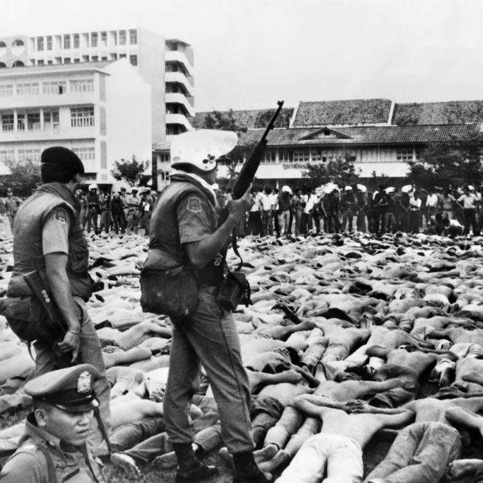 Shirtless students lie with hands behind their necks during the Thammasat University massacre on October 6 1976 in Bangkok