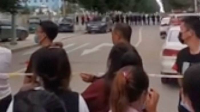 An image from a video taken last month shows parents gathering behind a police line outside a school in Tongliao, Inner Mongolia