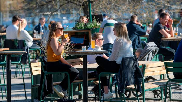 People socialise in Stockholm on April 22 as the country's approach to dealing with coronavirus comes under scrutiny