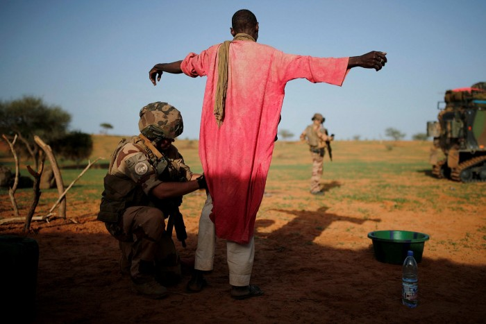 A French soldier searches a man during an area control operation in Ndaki, Mali, in 2019
